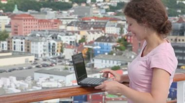 Woman types on netbook at deck of ship in port during cruise — Stock Video