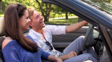 Boy and girl sit and laught in cabriolet at sunny summer day — Stock Video