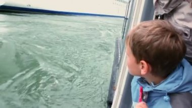 Boy watches on huge cruiser from which they float away on fiord — Stock Video