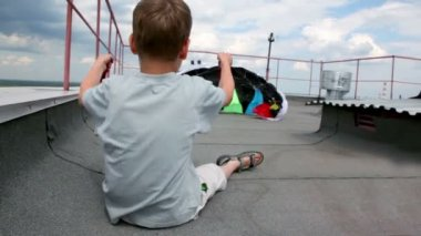 Boy sit on roof and hold shroud lines, parachute inflated by air — Vídeo Stock