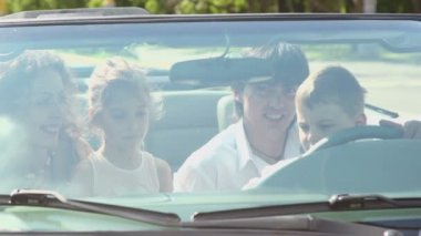 Kids sit on parents lap in cabriolet, view through front window — Stock Video