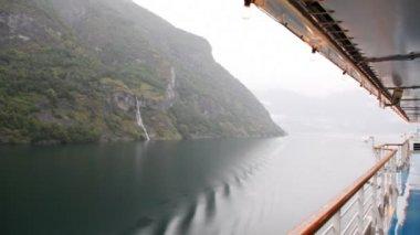 Skalnaté pobřeží dřevo od představenstva lodi plující na vodě — Stock video