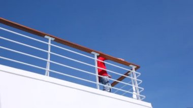 Boy waves greeting by hand standing on ship handrail against sky — 图库视频影像
