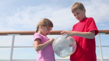 Two kids stand near railing and hold inflated ball — Vídeo Stock