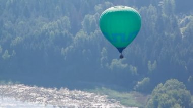 Balloon of green color flies far over the river and wood — Stock Video