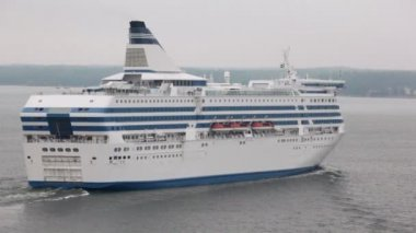 Huge cruise liner floats near coastline with forest and houses — Stock Video