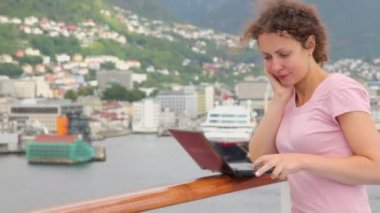 Woman pushes buttons on notebook at deck of ship which floats — Video Stock