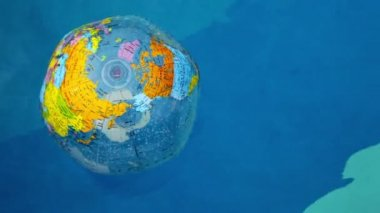 Inflated earth ball floats on wavy water surface in pool — Vidéo
