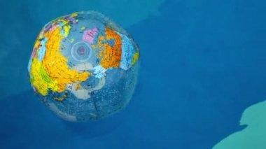 Uppblåsta jorden boll flyter på vågig vattenyta i poolen — Stockvideo