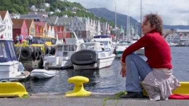 Woman sits and sings on quay in dock at coastal Bergen town — Stock Video