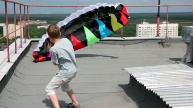 Boy stand and hold shroud lines, parachute inflated by air — Vídeo Stock