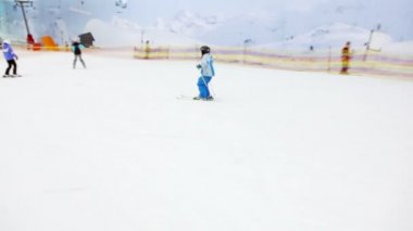Little boy slides on alpine skis from snowy slope — Stock Video