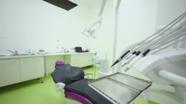 Dental tools and medical equipment near chair with tv set above — Stock Video