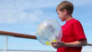 Little boy stand near railing and hold inflated ball — Vidéo