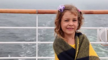 Little girl wrapped in plaid stands on deck during cruise — Stock Video
