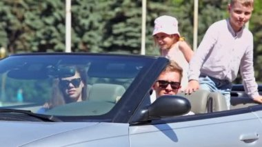 Young couple with kids ride backward in cabriolet at sunny day — Stock Video