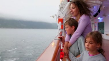 Mother and kids stand on ship deck which sail near coastline — Stock Video