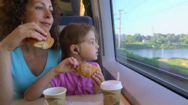 Mother with daughter eat marzipans and watch to train window — Stock Video