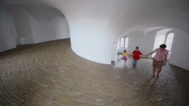Mother with two kids walk in spiral corridor with paved floor — Stock Video