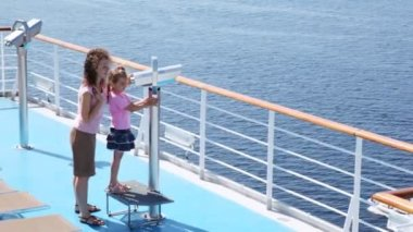 Girl looks in binocular on ship deck under direction of mother. — Stock Video