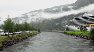 Camping on shore of river which flow into fiord with huge liner — Stock Video