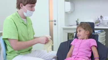 Dentist puts on gloves and girl watch him from dental chair — Stock Video