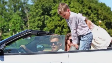Couple with kids sit in cabriolet, boy wag finger at kids behind — Stock Video