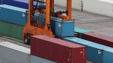 Reachstacker lifts one of several containers in port at day — Stok video