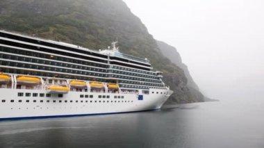 Board of huge multideck liner standing at rocky coast — Stock Video