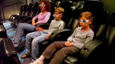 Mother with kids in 3d stereo glasses sit at cinema — Stock Video