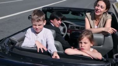 Parents and two kids seat in car and ride away at sunny day — Stock Video