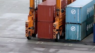 Machine with several wheels rides among containers at port — Stock Video