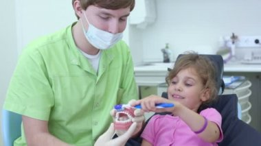 Dentist holds jaw and girl cleans teeth by brush — Vidéo