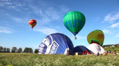 Balloons fly up in sky with passengers over green field — Stock Video