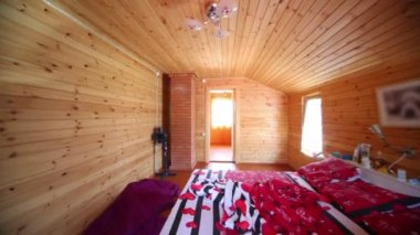 Bedroom in wooden house lit by light from windows — Stock Video