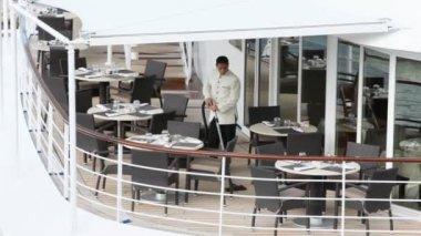 Servir en el piso blanco vacíos entre mesas en abierta cubierta de barco — Vídeo de stock