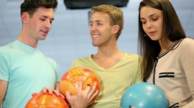 Two boy and one girl hold bowling balls and smile, closeup view — Stock Video
