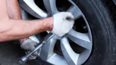 Man tight nuts on car wheel by cross screwdriver, closeup view — Stock Video