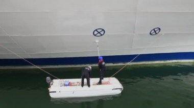 Two workers stand on small boat and paint board of huge ship — Stock Video