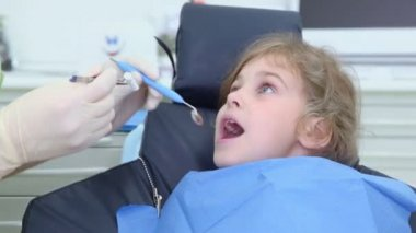 Dentist puts dental mirror in girls mouth — Stock Video