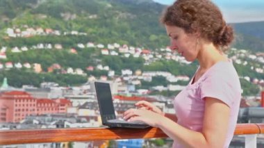 Woman pushes buttons on netbook at deck of ship in port — 图库视频影像