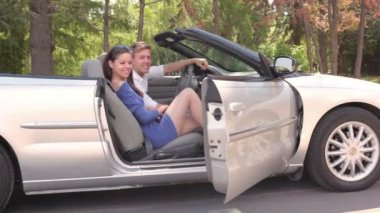 Young couple sit in cabriolet and girl closes door at summer day — Stock Video