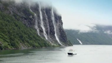 Ship floats by fiord near Seven Sisters waterfall on mountain — Stock Video