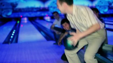 Man hold bowling ball, then throws it, friends encourage him — Stock Video