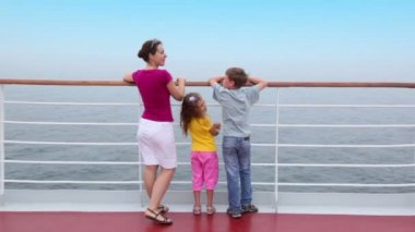 Mother with kids stand on deck near fence and admire seascape — Stock Video