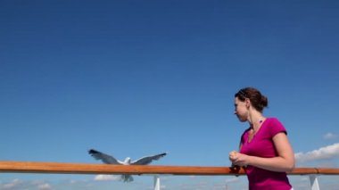 Woman feeds several gulls, she throws it and put on railing — Stock Video