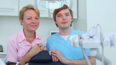 Nurse and doctor in uniform sit in dental surgery and smile — Vídeo de stock