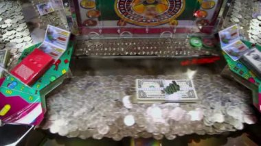 Play machine with many coins and dollars inside, closeup view — Stock Video