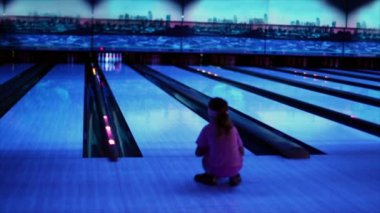 Girl watch on ball trundles by bowling lane and beats skittles — Stock Video