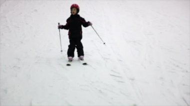 Little girl in helmet and warm clothes moves alpine skis — Stock Video